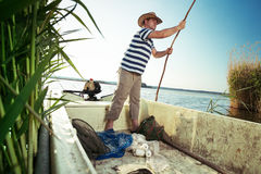 Fisherman pushing boat from the river bank Royalty Free Stock Photography