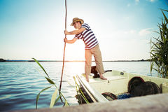 Fisherman pushing boat from the river bank Stock Photos