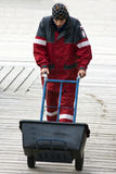 Fisherman pushing box. Fisherman wearing waterproof clothing pushing box on hand truck Stock Photos