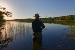 Fisherman. In the rays of the setting sun Royalty Free Stock Photo