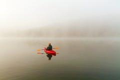 Fisherman in red kayak Stock Photo