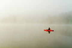 Fisherman in red kayak Stock Photography