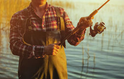 A fisherman in a red shirt is fishing for spinning in a freshwater pond. At sunset Royalty Free Stock Photo
