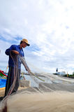 A fisherman is removing anchovies fish from his fishing net to begin a new working day in Ly Son island Stock Photography