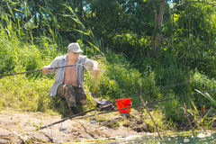 Fisherman removing his catch from the net Stock Photo