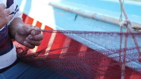 Fisherman is repair the fish net. Needle with thread in fisherman mouth until repairing net for angling stock video