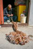 Fisherman repairing fishing net. With cords and floats royalty free stock image