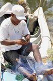 Fisherman repairing nets Stock Images