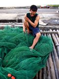 A fisherman repairs a fishing net before casting it out into the sea again. Stock Photography