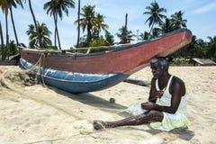 A fisherman repairs his nets on Arugam Bay beach on the east coast of Sri Lanka. Royalty Free Stock Image