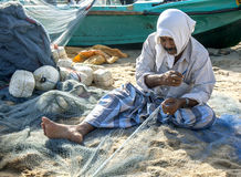 A fisherman repairs his nets on Arugam Bay beach in Sri Lanka. Royalty Free Stock Images