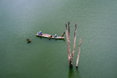 A fisherman rides long tail boat across Songkhalia river, Sangkhlaburi. A fisherman rides long tail boat across Songkhalia river, Sangkhlaburi, Kanchanaburi Stock Image