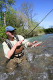 Fisherman in river catching trout Royalty Free Stock Photos