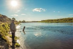 Fisherman in the river landscape at sunset. River landscape at sunset with fisherman on shore Royalty Free Stock Images