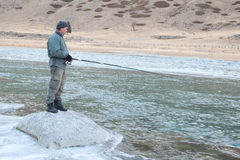A fisherman on the river in winter Royalty Free Stock Photography