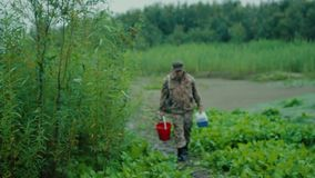 Fisherman on the road. The fisherman came out from behind the bushes on the path leading to the bank of the river stock video footage