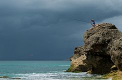 Fisherman catching an airplane on the rock stock images