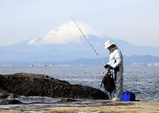 Fisherman on the rocks in the Pacific Ocean on Mount Fuji background. Nature of Japan. Kamakura, Japan, 01/06/2013 royalty free stock photo