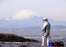 Fisherman on the rocks in the Pacific Ocean on Mount Fuji background. Nature of Japan. Kamakura, Japan, 01/06/2013 stock photo