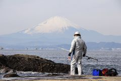 Fisherman on the rocks in the Pacific Ocean on Mount Fuji background. Nature of Japan. Kamakura, Japan, 01/06/2013 royalty free stock photography