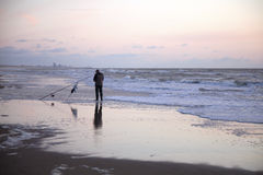 ​​fisherman with rod on the beach at sunset Stock Photography