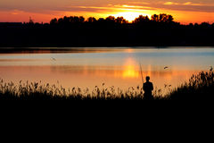 Fisherman with a rod fishing at sunset Royalty Free Stock Image