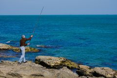 Fisherman with a rod on rocks in the sea Royalty Free Stock Images
