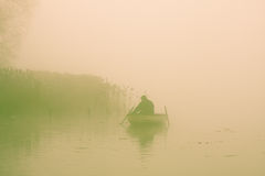 Fisherman in Rowboat. Fisherman prepares gear in rowboat on an early winter morning Stock Photos