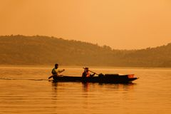Fisherman rowing for fish in the sunset stock image