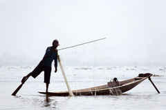 Fisherman at Inle Lake. A fisherman rowing with his foot on the still morning at Inle Lake in Myanmar Stock Images