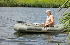 Fisherman rowing a rubber dinghy Royalty Free Stock Images