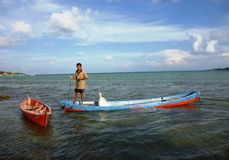 Fisherman rowing a sampan boat Royalty Free Stock Image