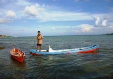 Fisherman rowing a sampan boat. In the islands of Java Karimun Royalty Free Stock Image