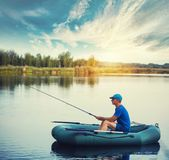 A fisherman in a rubber boat is fishing on the lake. At sunset stock photos