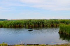 Fisherman in rubber boat on a river Royalty Free Stock Images