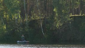 Fisherman in rubber boat throws a fishing pole with spoon-bait, jigs, spinner on river. Man stands and fishing on lake. In sunny forest stock footage