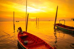 Fisherman`s boat floating in the sea near bamboo pole at sunset in Thailand. Royalty Free Stock Image