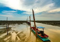 Fisherman`s boat parked at coastal mud flat at tide. Landscape of sea and beautiful blue sky and white clouds at sunset. Mud beach.  stock photos
