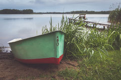 Fisherman`s boat at rainy evening with bridge in background Royalty Free Stock Image