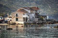 Peaceful morning in little harbour. Fisherman`s boats and old stone houses in port of Komiza on island Vis in Croatia stock image