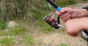 Fisherman`s fishing rod with inertia-free coil in summer on shore of lake close up. 4K stock footage
