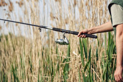 Fisherman`s hand holding fishing rod. With reel Stock Images