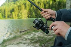 Closeup of Fisherman s hand with spinning - summer fishing season. stock photos