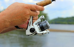 Fisherman`s hand with spinning  Royalty Free Stock Photo