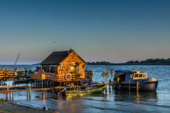 Fisherman's House, the old dock and the boat on the lake. Rustic. Landscape with wooden pier in the summer evening Royalty Free Stock Photography
