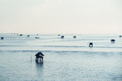 Fisherman`s huts in the blue sea Stock Photos