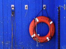 Fisherman's Life Ring. A life ring nestled alongside a blue warehouse Royalty Free Stock Images