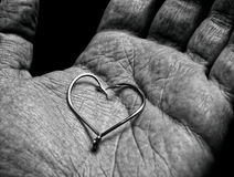 Fisherman's love. Shape or symbol of a heart in hand of an old fisherman Royalty Free Stock Photo
