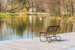 A fisherman`s place on the shore of the lake on a clear, sunny day in the spring. Places for fishing rods, fishing seat, wooden pi. This picture was taken in stock photography