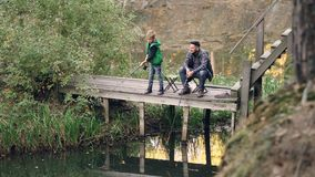 Fisherman`s son cute kid is fishing with his father from wooden pier holding rod while proud parent is looking at his. Child and talking to him. Parenthood stock video footage